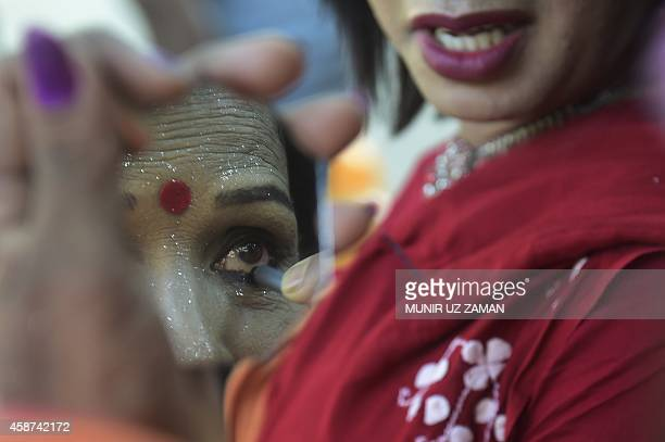 A Bangladeshi hijra transgender applies pencil eyeliner prior to a rally marking the first ever nationwide program to observe 'Hijra Day' in Dhaka on...