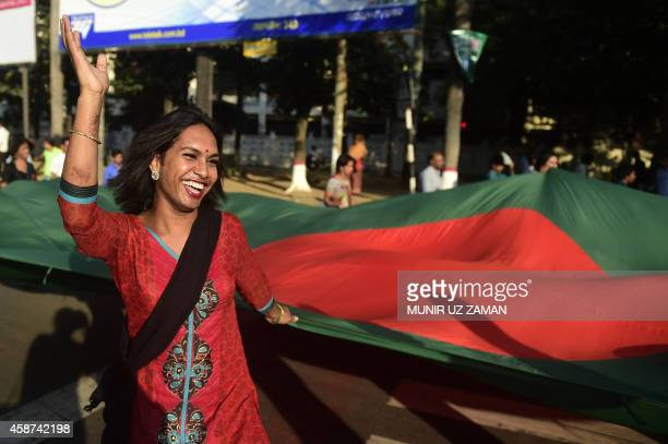 A Bangladeshi hijra transgender holds a national flag as she dances during a rally to mark the first ever nationwide program to observe 'Hijra Day'...