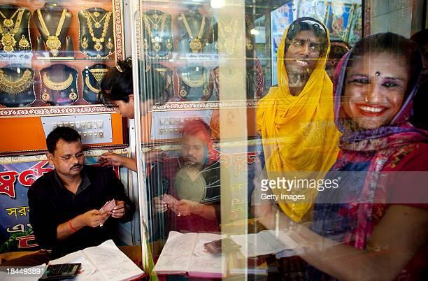 Bangladeshi Hijras go door to door to businesses demanding tips on the last day of Durga Puja in Old Dhaka October 14 2013 in Dhaka Bangladesh Hindus...