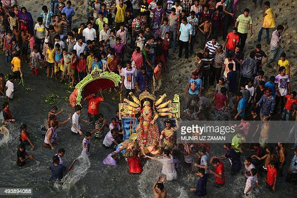 Bangladeshi Hindu devotees prepare to submerge a clay idol of the Hindu goddess Durga on the final day of the Durga Puja festival in Dhaka on October...