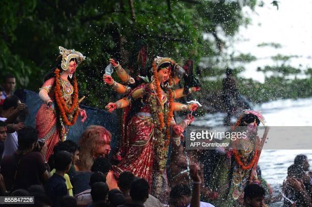 Bangladeshi Hindu devotees submerge a clay idol of the Hindu goddess Durga on the final day of the Durga Puja festival in Dhaka on September 30 2017...