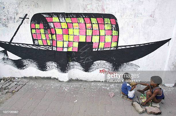 Bangladeshi homeless children play in front of a painted boat the logo of the opposition party Awami League in Dhaka 17 November 2006 Bangladesh...