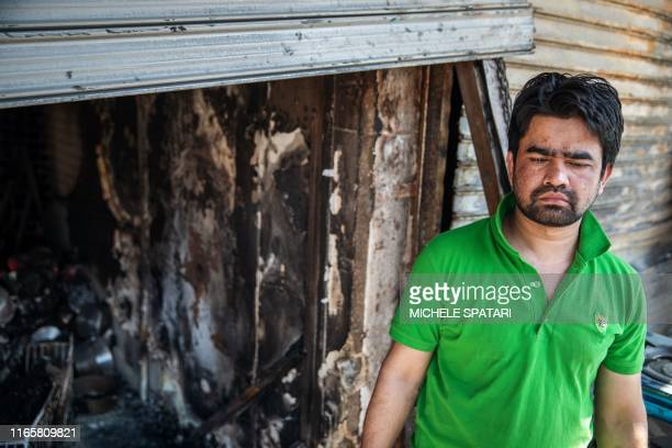 Bangladeshi Kamrul Hasan stands by his looted shop in the Johannesburg township of Alexandra on September 3 2019 after South Africa's financial...