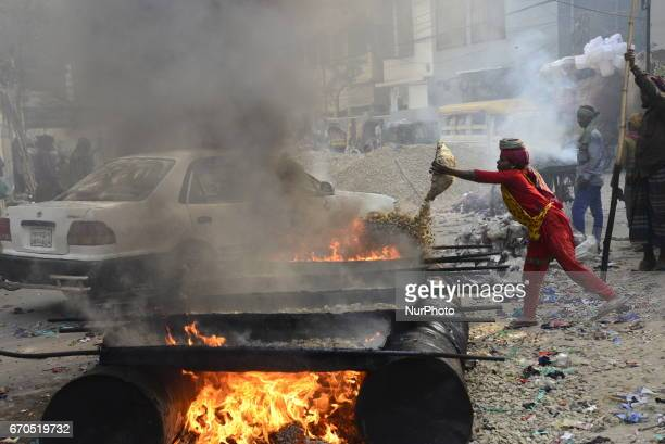 Bangladeshi laborers mix stone chips with Bitumen for road repair at residential area in Dhaka City Bangladesh on April 18 2017