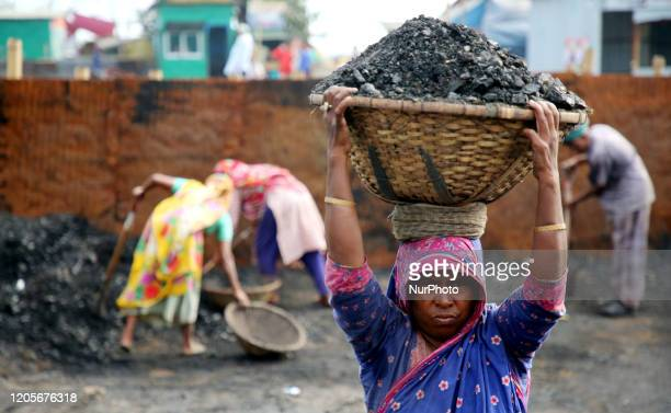 Bangladeshi laborers unload coal from boats ahead of International Women's Day at the River Turag in Dhaka Bangladesh on March 7 2020