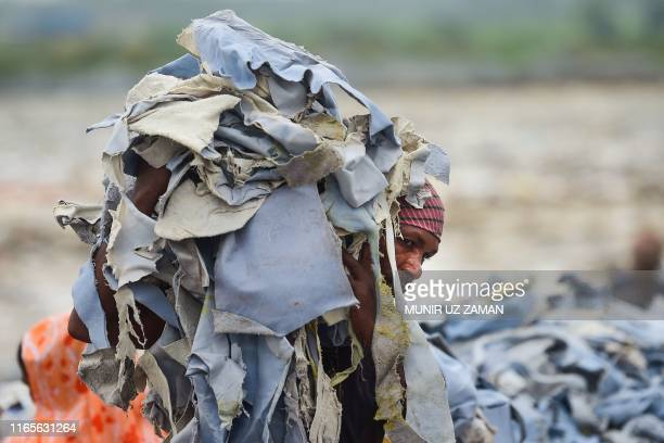 A Bangladeshi labourer carries a pile of tannery waste at an export processing zone in Savar on September 2 2019