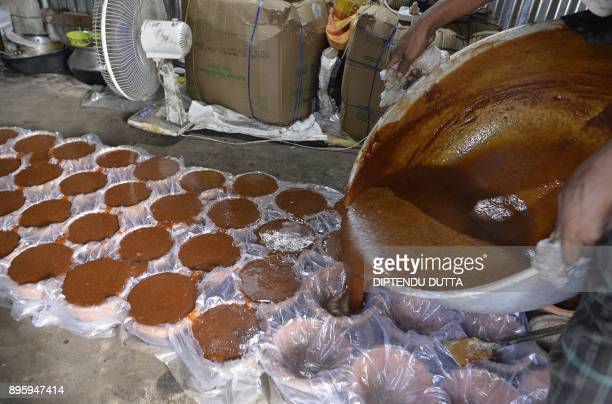Bangladeshi labourer Rahim Sheikh fills pots after preparing jaggery 'cane sugar' from the sap of the date palm tree in Dodhiabari village near...