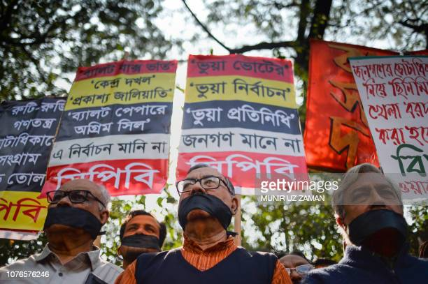 TOPSHOT Bangladeshi leftwing activists organised by the Communist Party of Bangladesh wear black cloth over their mouths at a protest against the...