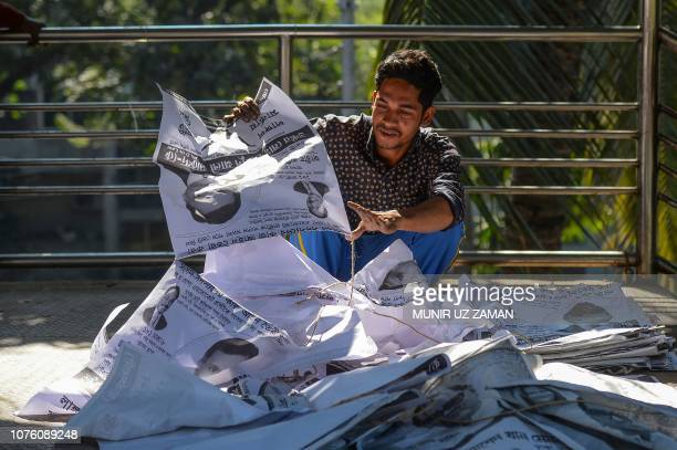 A Bangladeshi man gathers election posters in Dhaka on December 31 a day after the country's general election Bangladesh Prime Minister Sheikh Hasina...