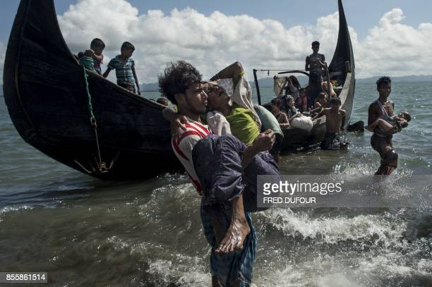 Bangladeshi man helps Rohingya Muslim refugees to disembark from a boat on the Bangladeshi shoreline of the Naf river after crossing the border from...