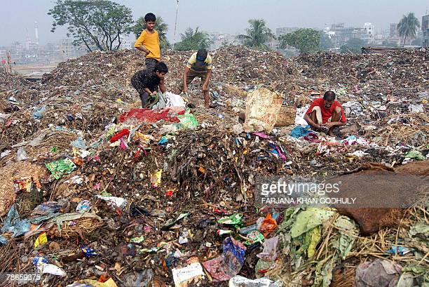 Bangladeshi man Khurul Ali collects various materials from a garbage yard along with his sons at Kamrangir chor on the outskirts of Dhaka 27 December...