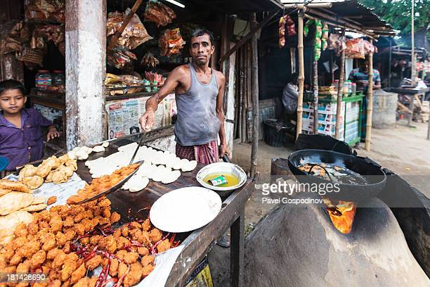 CONTENT] Bangladeshi man preparing Samosas and other street food on a primitive clay oven directly on the street rural Bangladesh around Srimangal...