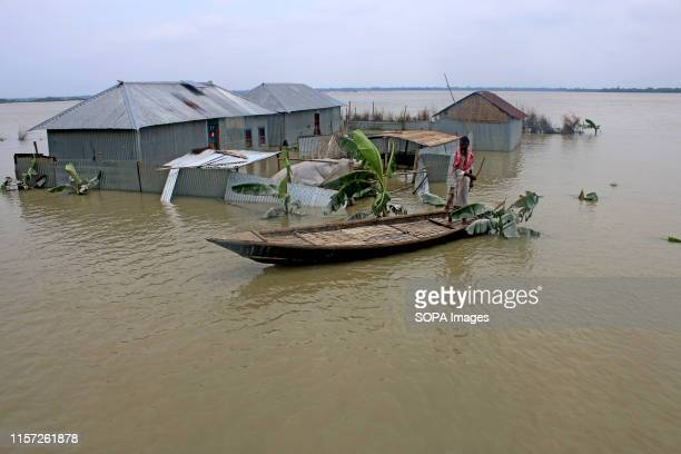 Bangladeshi man pulls a small boat in front of his house through flood waters following heavy mosoon rains in Tangail Over million people have been...