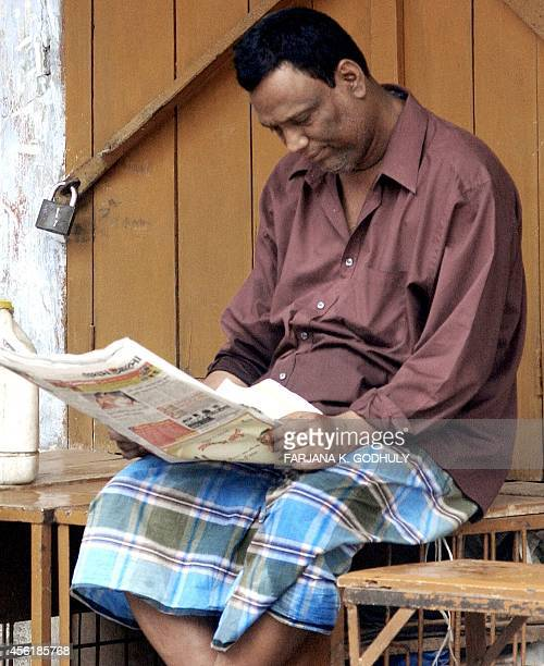 A Bangladeshi man reads a newspaper as he sits in front of locked shop during a traders strike in Dhaka 30 March 2004 A major Bangladeshi business...