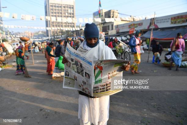 Bangladeshi man reads a newspaper carrying headlines of the general election results in Dhaka on December 31, 2018. - Bangladesh Prime Minister...