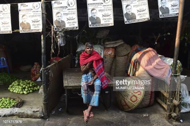 Bangladeshi man sits on his rickshaw van as posters of the ruling Bangladesh Awami League election candidates hang above him at a market in Dhaka on...