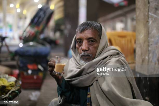 A Bangladeshi man takes tea at a street tea stall during cold weather in Dhaka Bangladesh on December 19 2018 More than 100 million people are...