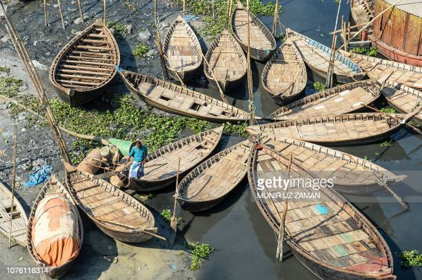 A Bangladeshi man walks over a boat hold in position in Buriganga River in Dhaka on December 31 a day after the country's general election Bangladesh...