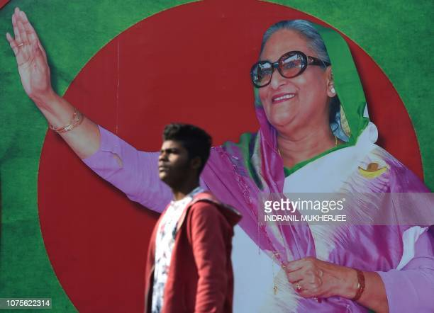 A Bangladeshi man walks past a photo of Prime Minister Sheikh Hasina in Dhaka on December 29 2018 Bangladesh stepped up security on December 29 in a...