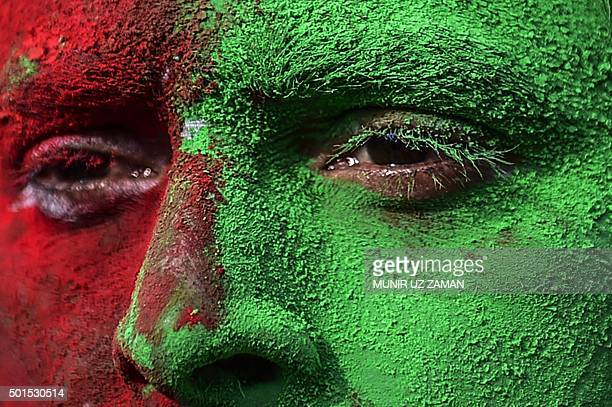 A Bangladeshi man with his face painted in the colours of the national flag takes part in a rally to mark the country's 44th Victory Day in Dhaka on...