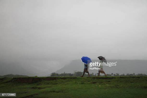 Bangladeshi men hold umbrellas to protect themselves from rain walk alone a river side during the rainy day at Bisanakandi in Sylhet Bangladesh near...