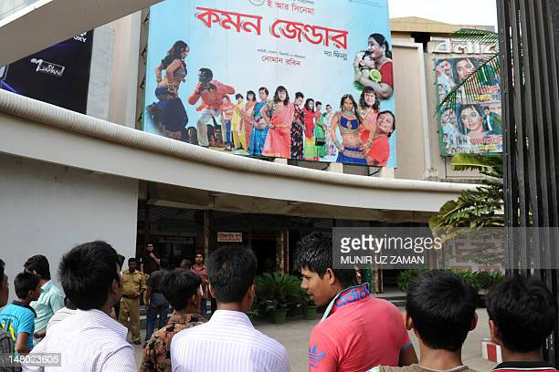 Bangladeshi men look at a billboard advertising the film Common Gender at a movie theatre in Dhaka on July 6 2012 A film about a love affair between...