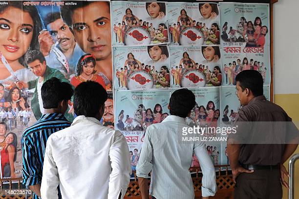 Bangladeshi men look at a poster advertising the film Common Gender at a movie theatre in Dhaka on July 6 2012 A film about a love affair between a...