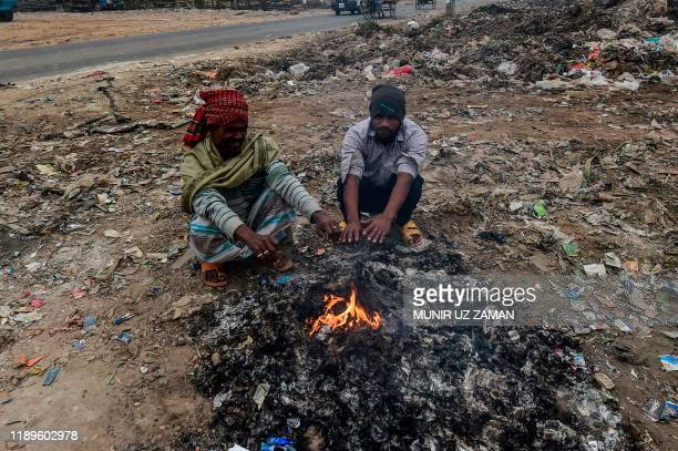 Bangladeshi men warm themselves around a bonfire on a cold day in Dhaka on December 19, 2019.
