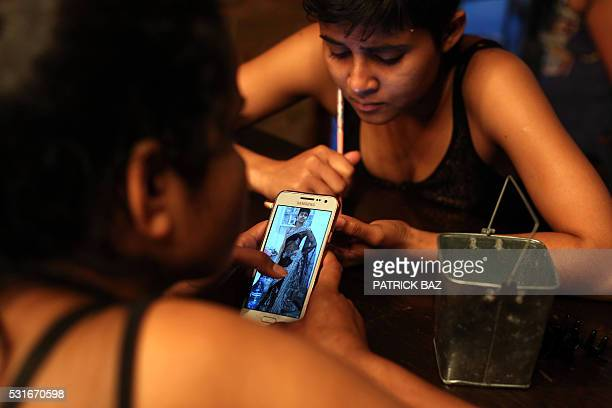 A Bangladeshi migrant helper Sumy Khan and an unidentified colleague look at fashion pictures on their phones as they prepare to take part in a...
