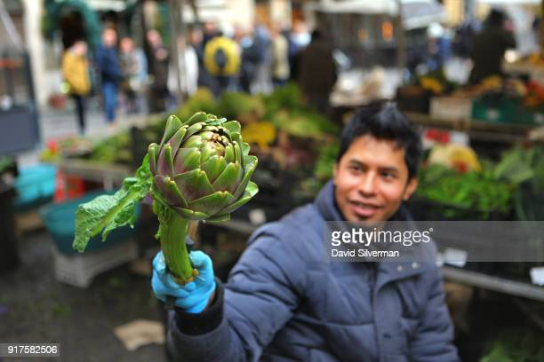 Bangladeshi migrant worker cleans fresh artichokes in a produce stall at the iconic Campo di Fiori market on December 9 in Rome Italy Chronicallypoor...