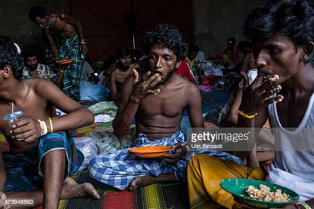 Bangladeshi migrants breakfast at a temporary shelter on May 19 2015 in Kuala Langsa Aceh province Indonesia Hundreds of Myanmar's Rohingya refugees...