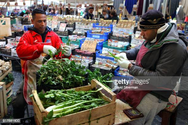 Bangladeshi migrants clean fresh produce as they work in a produce stall at the iconic Campo di Fiori market on December 9 in Rome Italy...
