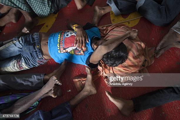Bangladeshi migrants sleep on the floor of a warehouse in Kuala Langsa Port in Langsa Aceh province Indonesia on May 17 2015 Hundreds of Rohingya and...