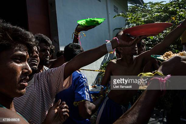 Bangladeshi migrants take their breakfast at a temporary shelter on May 19 2015 in Kuala Langsa Aceh province Indonesia Hundreds of Myanmar's...