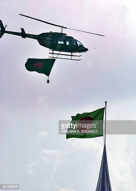 Bangladeshi military pilot flies with a national flag hanging from his helicopter during an acrobatic display as part of the Independence Day...