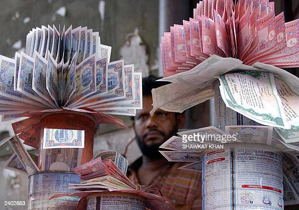 A Bangladeshi money dealer displays clean bundles of Taka the country's currency in his shop in Dhaka 07August 2003 Many of the notes which are in...