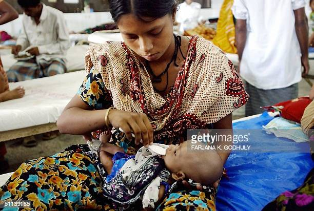 Bangladeshi mother feeds her baby with saline mixture at Dhaka medical college hospital 03 August 2004 As many as 30 million people in Bangladesh hit...