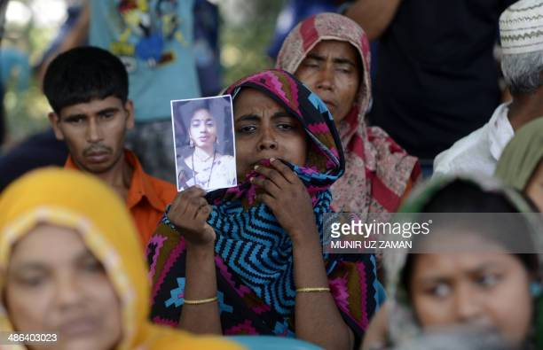 Bangladeshi mourner and relative of a victim of the Rana Plaza building collapse holds up a photograph as she takes part in a protest marking the...