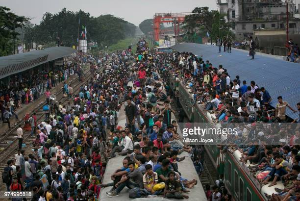 Bangladeshi Muslims climb on overcrowded trains to travel home for Eid alFitr on June 15 2018 in Dhaka Bangladesh Muslims around the world celebrate...