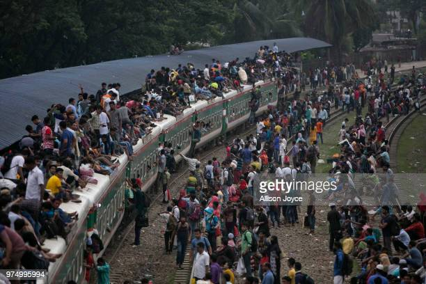 Bangladeshi Muslims climb the roof of an overcrowded train to travel home for Eid alFitr on June 15 2018 in Dhaka Bangladesh Muslims around the world...