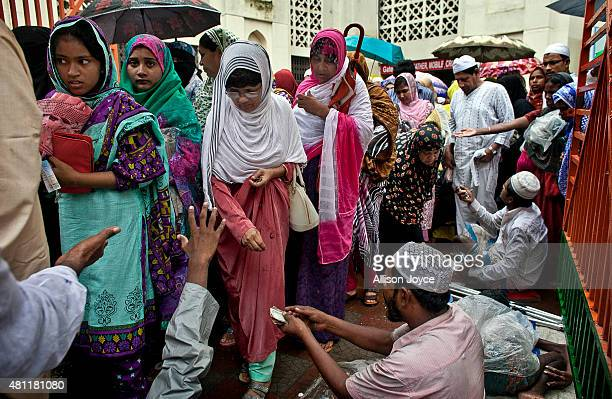 Bangladeshi Muslims give alms to beggars after prayers at Baitul Mukarram the National Mosque on Eid AlFitr July 18 2015 in Dhaka Bangladesh Muslims...