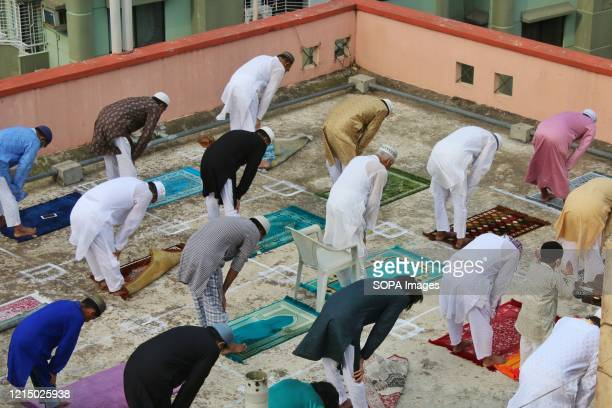 Bangladeshi Muslims perform Eid alFitr prayers on the rooftop of a residential building while keeping a safe distance amid Coronavirus crisis Eid is...