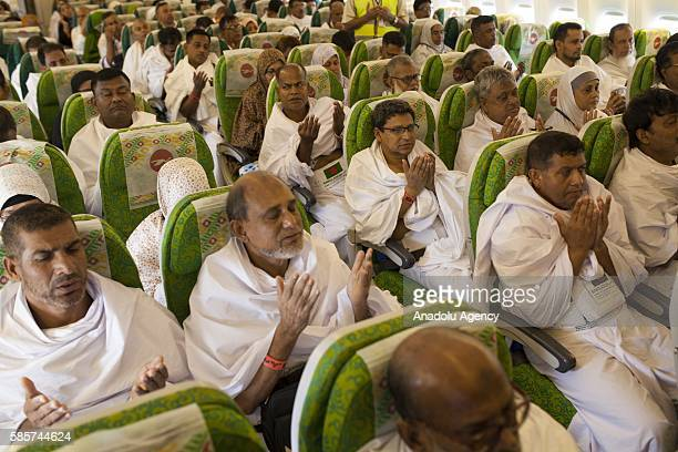 Bangladeshi Muslims pray before the plane takes off during their journey from Dhaka to Mecca for making a pilgrimage at Shahjalal International...