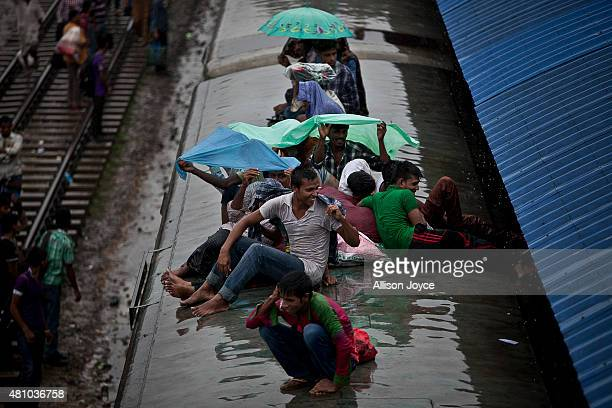 Bangladeshi Muslims ride atop a train during a downpour to head home to their respective villages ahead of Eid AlFitr July 17 2015 in Dhaka...