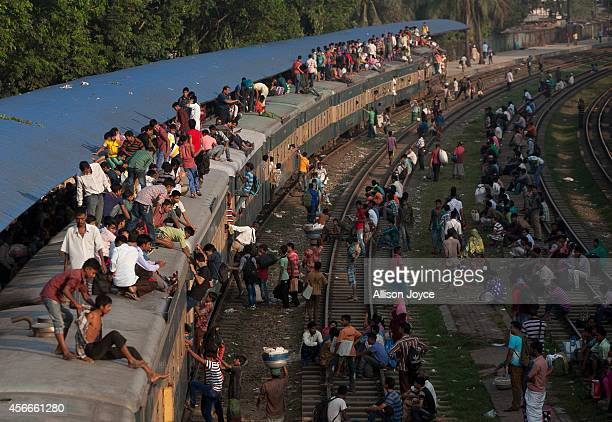 Bangladeshi Muslims ride on the roof of an overcrowded train as they head to their homes the day before the EidalAdha Festival October 5 2014 in...