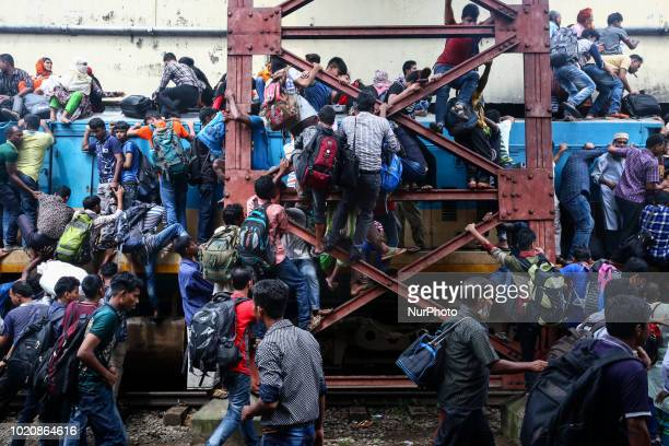 Bangladeshi Muslims sit on the roof of an overcrowded train to travel home for Eid al-azha celebration at railway station in Dhaka, Bangladesh, on...