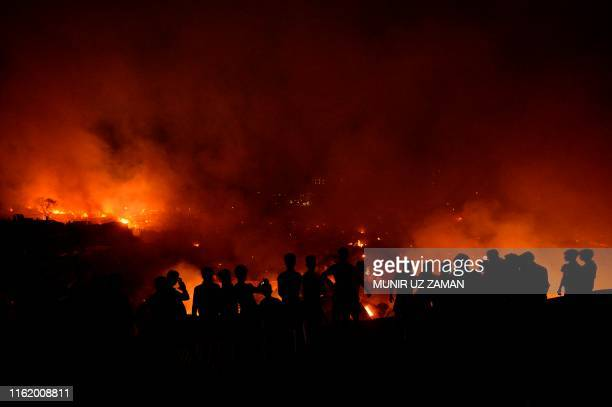Bangladeshi onlookers gather after a fire blazes in a slum in Dhaka on August 16, 2019. - At least 1,000 shanties were gutted as the devastating fire...