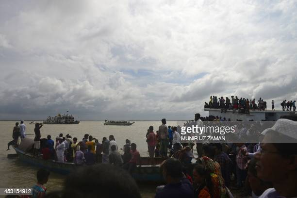 Bangladeshi onlookers gather near the scene where an overloaded ferry capsized in the Padma river in Munshiganj some 30 kilometres south of the...