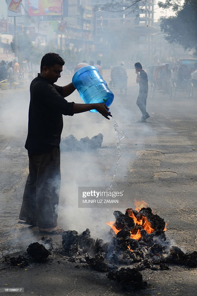 A Bangladeshi pedestrian tries to put out a fire started by Jamaat-e-Islami activists during a protest in Dhaka on February 12, 2013. The protesters hurled home-made bombs and attacked vehicles with bricks as police fought back with rubber bullets and tear gas in Dhaka's busy Karwan Bazaar and Motijheel commercial districts, police and witnesses said. AFP PHOTO/ Munir uz ZAMAN