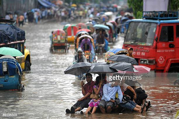 Bangladeshi pedestrians holding umbrellas hitch a ride on a rickshaw van as they attempt to stay dry over flood waters in the Bangladeshi capital of...